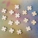 Pack of 16 Natural Wooden Puzzle Piece Card Topper Embellishments, as shown